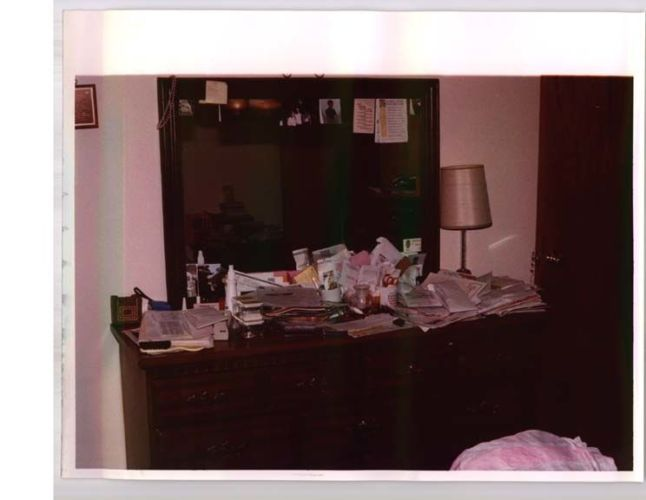 wide shot of dresser covered in papers and stuff