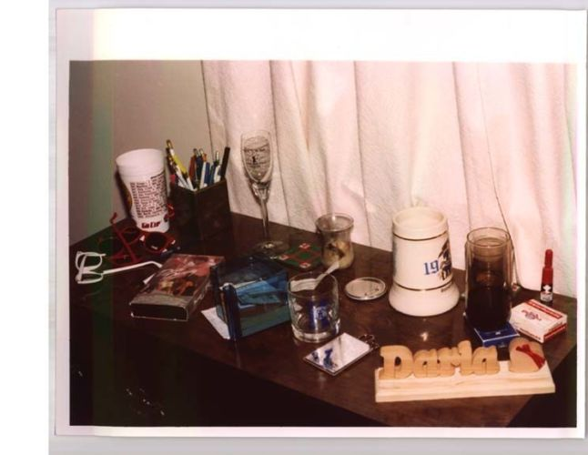 dresser covered in cups, sunglasses, and other knick knacks
