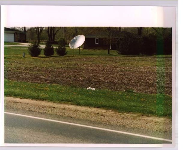 wide shot of white material in the grass near a road